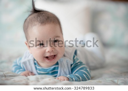 Cute 5 month old mixed race Asian Caucasian baby boy plays happily on a bed. Adorable happy expressions, blue clothes and indoor aqua coloured background. Very shallow, soft focus effects - stock photo