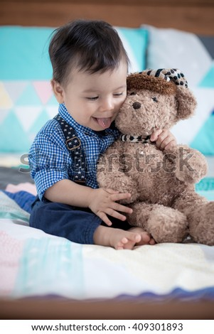 Cute 11 month old mixed race Asian Caucasian boy dressed in braces and bow tie cheerfully cuddles his brown teddy bear on a colourful geometrically shaped bed cover - stock photo