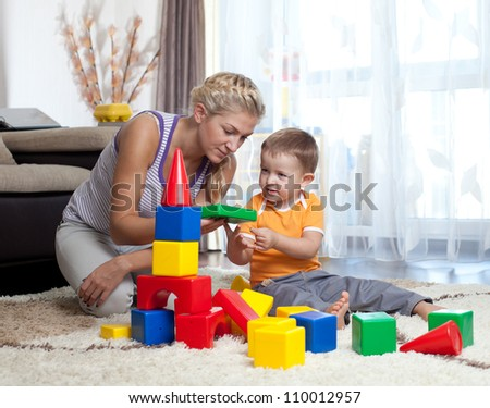 cute mother and child boy playing together indoor - stock photo