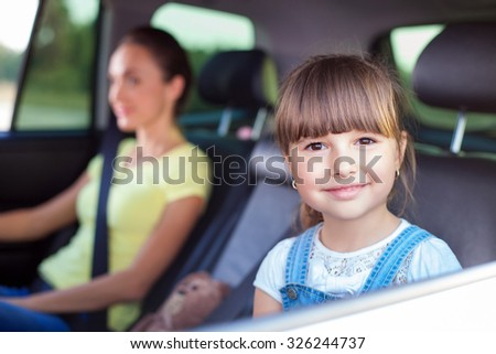 Cute mother and her daughter are traveling by car. They are sitting on back seat and smiling. The girl is looking through window happily - stock photo