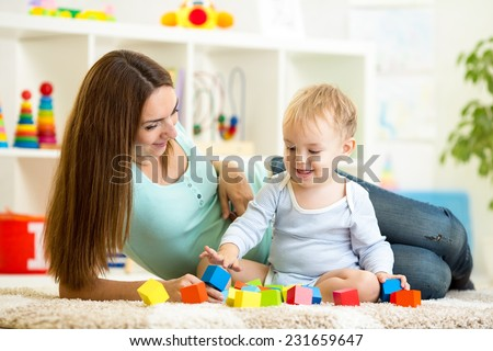 cute mother and her son play together indoor - stock photo