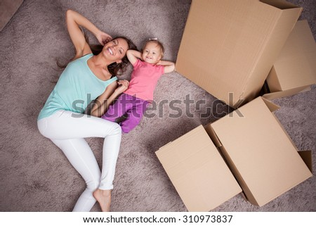 Cute mother and little daughter are lying on floor near boxes. They are preparing to move in another building. The parent and child are relaxing and smiling - stock photo