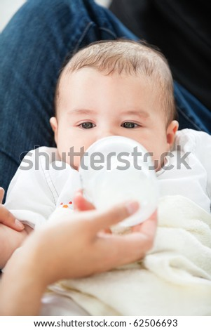 Cute mother feeding her adorable son in the kitchen at home - stock photo