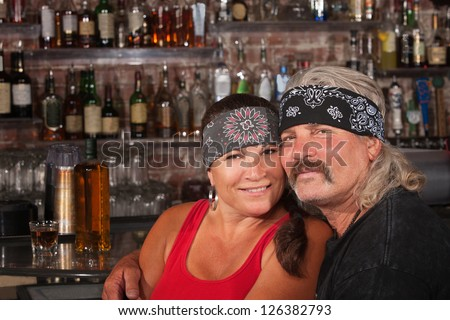 Cute motorcycle gang husband and wife together in bar - stock photo