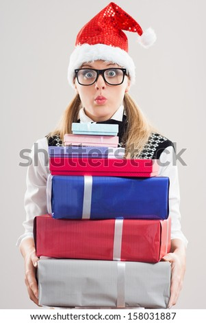 Cute nerdy woman is holding a lot of gifts and she is very excited,she can`t wait to open them,It`s time for presents! - stock photo