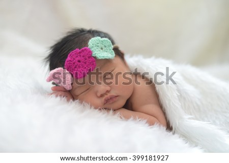 Cute newborn asian girl sleeping on furry cloth - stock photo