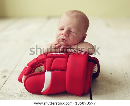 Cute newborn baby boy sleeping on a hockey glove - stock photo