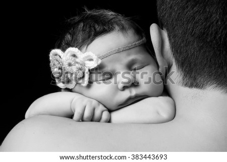 Cute newborn baby girl with knitted headband sleeping on dad's shoulder.  Studio, black background - stock photo