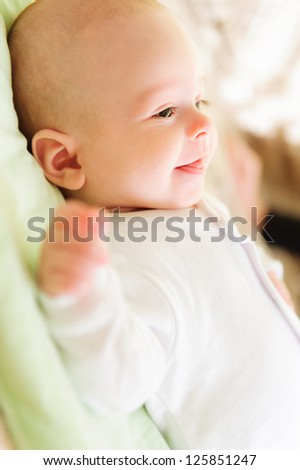 Cute newborn baby lying in bed and smiling - stock photo
