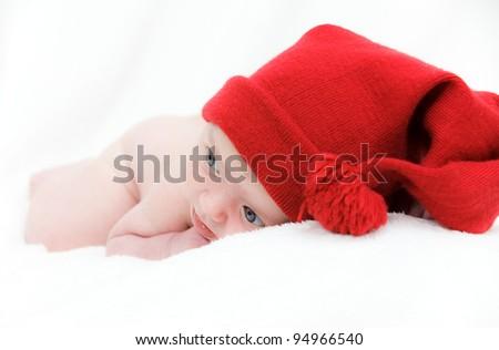 Cute newborn baby sleeps in a hat - stock photo
