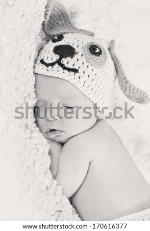 cute newborn baby sleeps in a knitted hat dogs ( black and white ) - stock photo