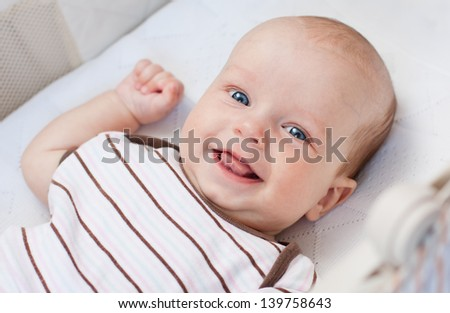 Cute newborn baby smiling looking at the camera - stock photo