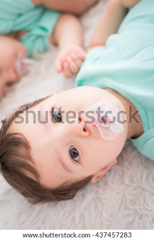 Cute Newborn baby twins smile to you with pacifier. Closeup portrait, caucasian child - stock photo