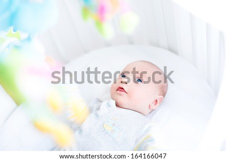 Cute newborn baby watching colorful toys in his white crib - stock photo
