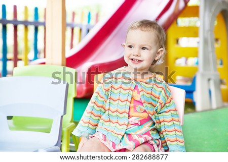 Cute nice smiling little girl on outdoor playground - stock photo