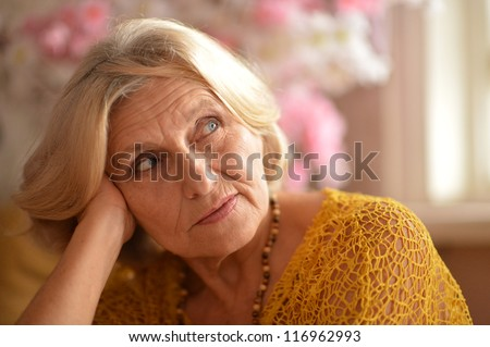 cute older woman poses in a room - stock photo