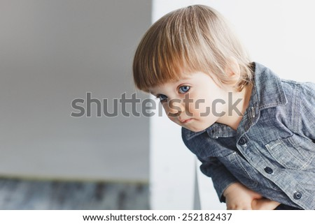 cute one year old baby boy peeking out at something - stock photo