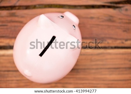 Cute Piggy Bank on the Wooden Table. Top view. - stock photo