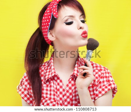 Cute pin up girl applying blusher - stock photo