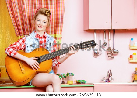 Cute pin-up girl teenager playing guitar on a pink kitchen. Beauty, youth fashion. Pin-up style. - stock photo