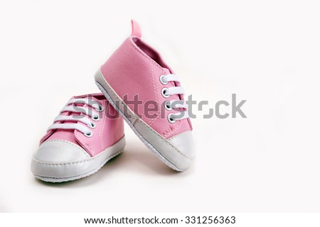 Cute pink baby girl sneakers close up on gray background - stock photo