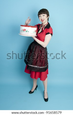 Cute pinup model holding a vintage cake pan - stock photo
