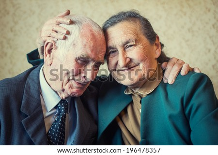 Cute 80 plus year old married couple posing for a portrait in their house. Love forever concept.  - stock photo
