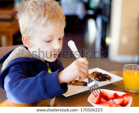 cute positive boy eating strawberries and pancakes at breakfast - stock photo