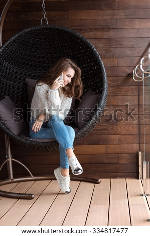 Cute positive girl sitting in bubble chair and talking on the cell phone  - stock photo