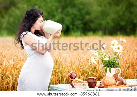 cute pregnant girl drinks milk in a field - stock photo
