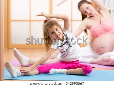 Cute pregnant mother and child daughter doing exercise at home - stock photo