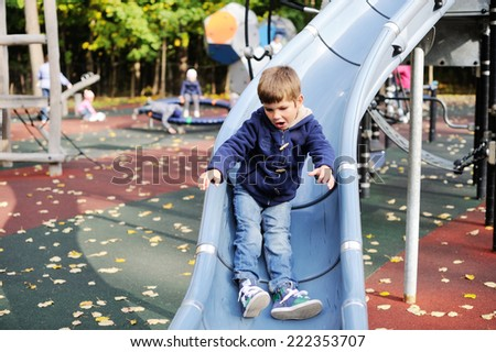 Cute prescholler boy excitedly plays on a grey playground slide on a cool sunny autumn day - stock photo