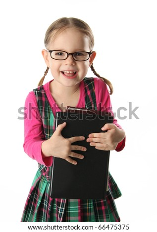 Cute preschool age girl wearing eyeglasses carrying a stack of heavy books - stock photo