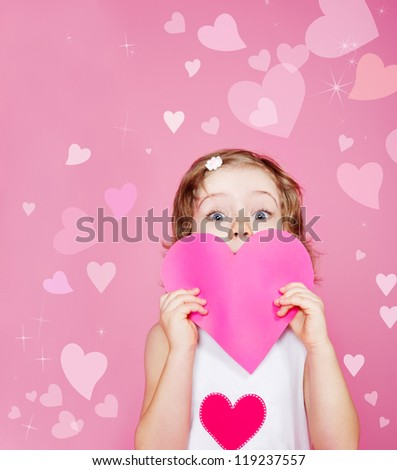 Cute preschool girl holding pink paper heart in hands - stock photo