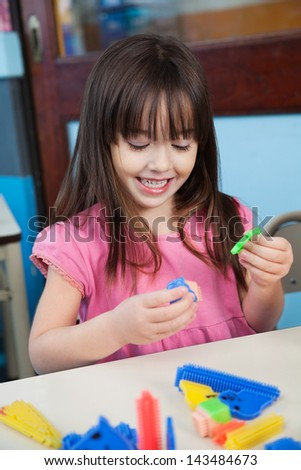 Cute preschool girl playing with construction blocks at desk in classroom - stock photo