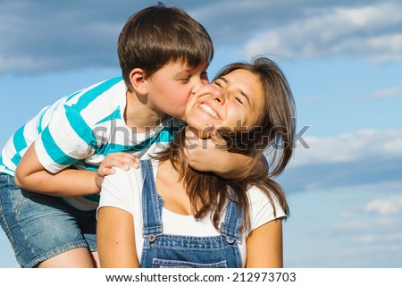 Cute preschooler boy hugging and kissing his older sister, a teenager on a background of blue sky in summer - stock photo