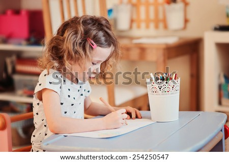 cute preschooler child girl drawing with pencils at home  - stock photo