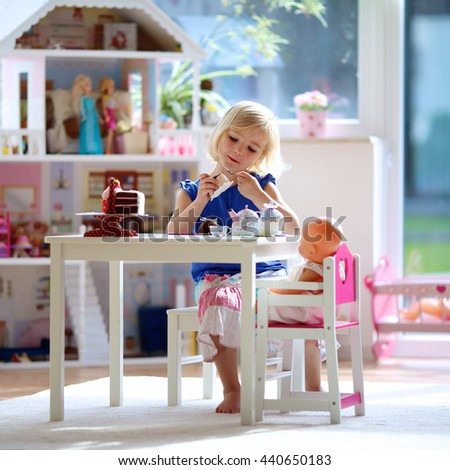 Cute preschooler girl having birthday tea party with her doll. Little child plays in sunny room at home or kindergarten. Kids using toy dishes and cakes. - stock photo