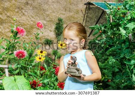Cute preschooler girl portrait with natural flowers in the garden - stock photo