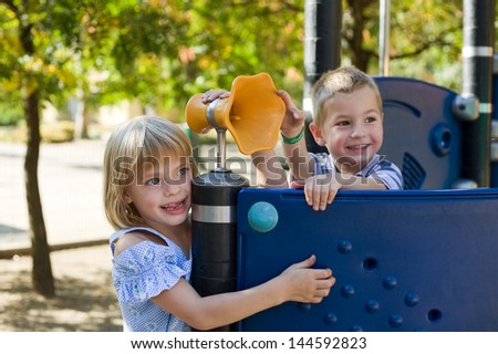 Cute preschoolers playing at the playground. - stock photo