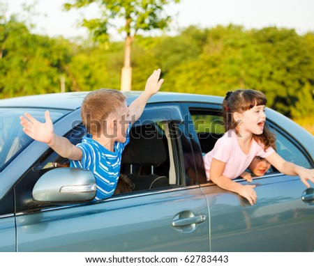 Cute preschoolers shouting from the car windows - stock photo