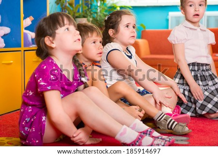 Cute preschoolers sitting on floor and listening to tutor - stock photo