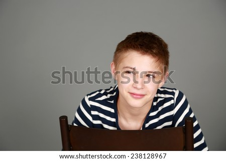 cute preteen blond boy smiling and looking to side and smiling - stock photo