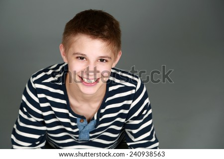 cute preteen blond boy with nice teeth smiling - stock photo