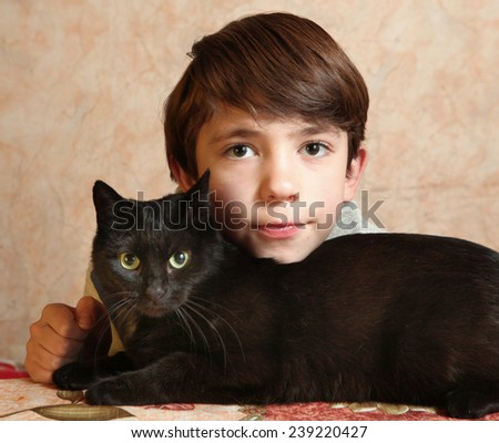 cute preteen boy with black cat - stock photo