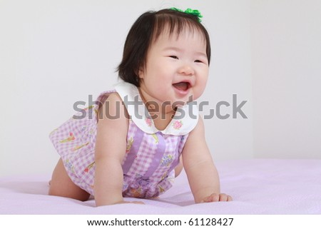 Cute Pretty Eleven Month Old Asian Infant Baby Girl in Purple and White Dress Leaning Crawling Forward and Smiling - stock photo