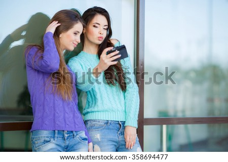 Cute pretty girls making funny selfie on the street, kissing to the cheek, having fun together, joy, positive, love, friendship, sisters.Girlfriends Taking Self Portrait with Their Phone Camera  - stock photo