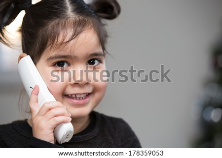 Cute pretty little girl in pigtails using the telephone giving the camera a beaming friendly smile, with copyspace - stock photo