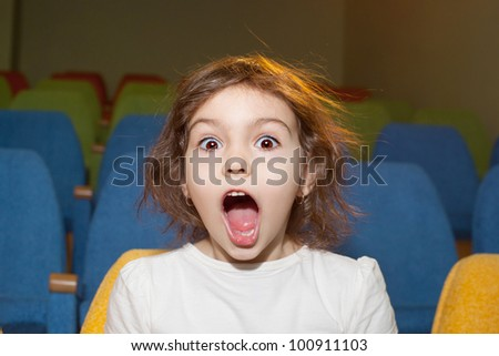 cute pretty little girl sitting in the cinema hall - stock photo