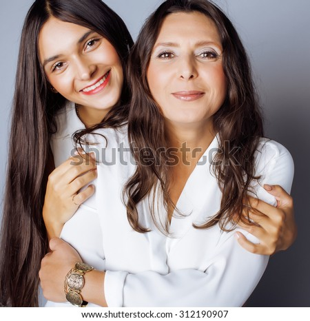 cute pretty teen daughter with mature mother hugging, fashion style brunette makeup - stock photo